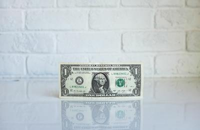 american dollar in front of brick wall
